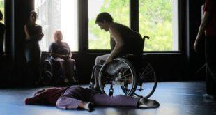 Escena de baile entre una persona en silla de ruedas y otra acostada en el suelo boca abajo