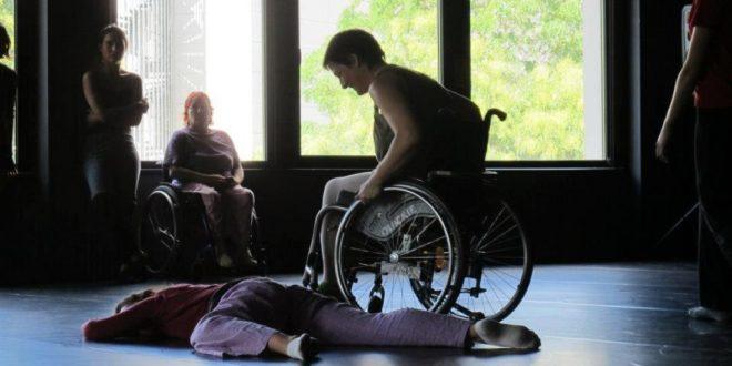 Escena de baile con una persona en silla de ruedas rodeando a otra acostada en el suelo