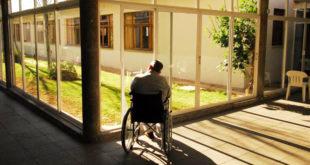 Hombre en silla de ruedas observando un patio interior